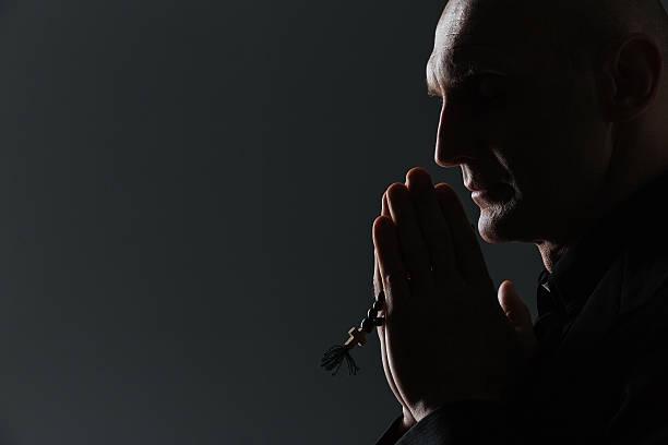 silhueta de homem segurando de terço e orar - padre - fotografias e filmes do acervo