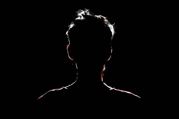 silhouette des menschen an dunklem ort, anonyme hinterleuchtete kontur a - gegenlicht stock-fotos und bilder