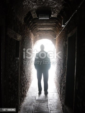 istock Silhouette of Man in Dark Tunnel with Light at End 157168380