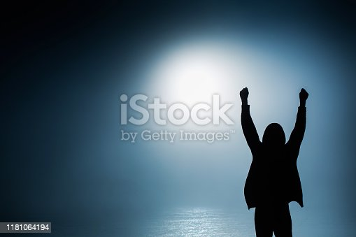 Silhouette of man in darkness. Business success. Mysterious anonymous figure. Triumph and victory. Incognito person in hoody. Successful person raise hand. Silhouette of man in hood. Liberty concept
