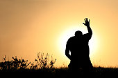 A man lifts his hand towards heaven. Silhouette, rear view, unrecognizable person. Additional themes include salvation, god, praise and worship, holiness, righteousness, faith, sin, forgiveness, gratitude, meditation, prayer, self, asking, pleading, hope, heaven, healing, spirituality, balance, religious, and Christianity.