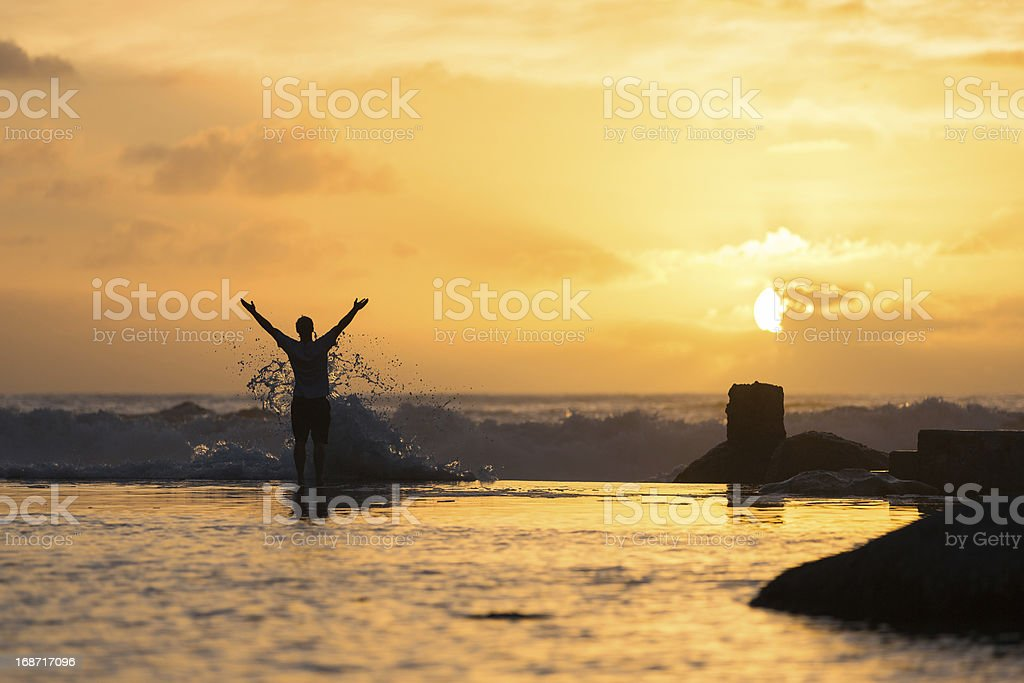 Silhouette of Man in Surf at Sunset stock photo