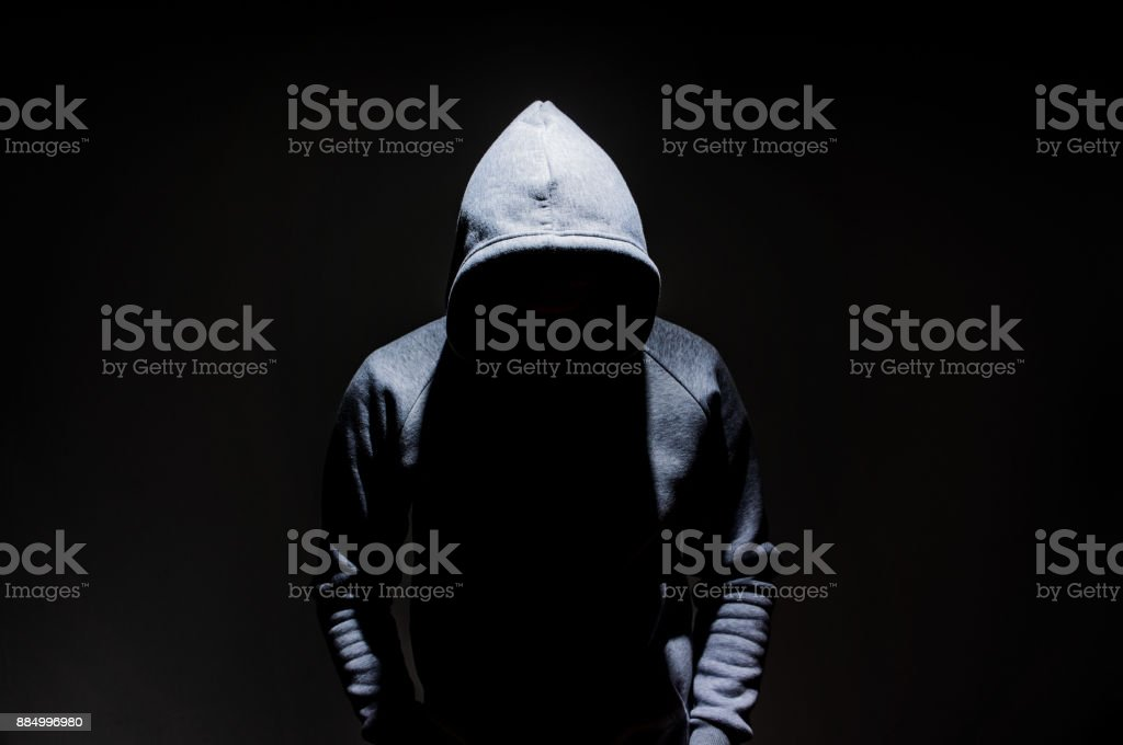 Silhouette of man in the hood, dark mysterious man hoodie, murderer, hacker, anonymus on the black background with free space - fotografia de stock