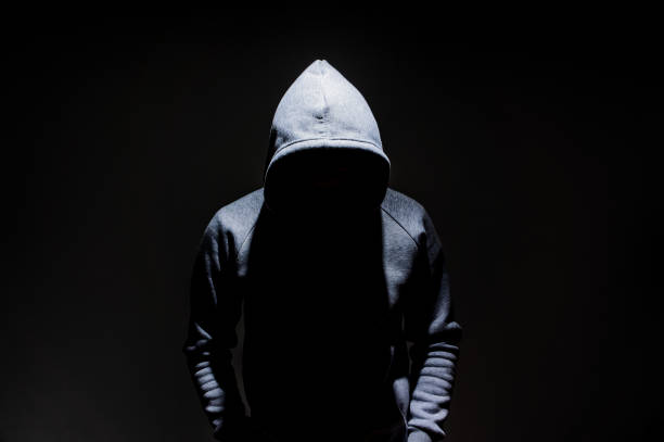 Silhouette of man in the hood, dark mysterious man hoodie, murderer, hacker, anonymus on the black background with free space stock photo