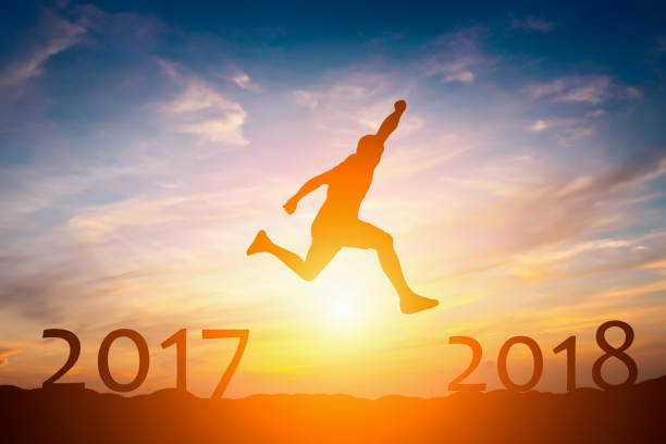 Silhouette of  man jump from 2017 to 2018 success concept in sunset stock photo