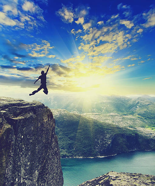 silhouette of man jumping on top of Norway mountain stock photo