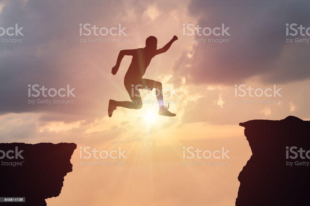 Silhouet van man springen over een kloof bij zonsondergang. foto