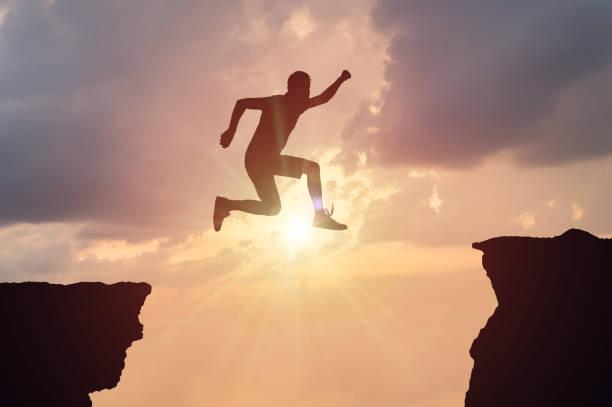 silhueta do homem pulando de uma lacuna ao pôr do sol. - despedida - fotografias e filmes do acervo