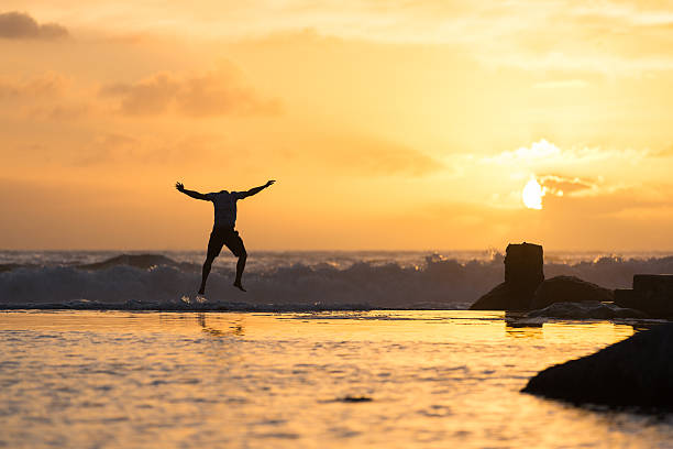 Silhouette of Man Leaping Up While Looking Down stock photo