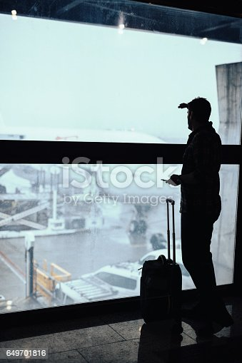 509630674 istock photo Silhouette of man looking in distance through the window at the airport 649701816