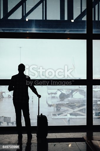 494216846 istock photo Silhouette of man looking through the window at the airport 649703998