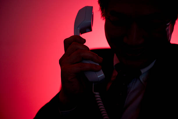 Silhouette of man making a phone call stock photo