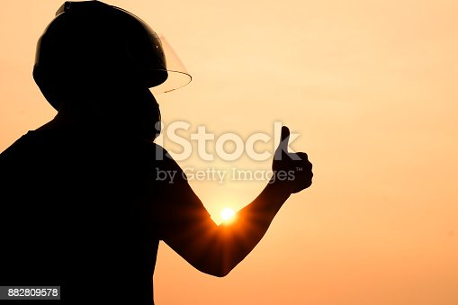 istock silhouette of man Motorcyclists wearing helmets Give a thumbs up to the sunset, the concept of success, or the winner 882809578