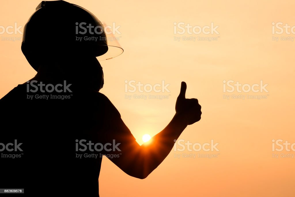 silhouette of man Motorcyclists wearing helmets Give a thumbs up to the sunset, the concept of success, or the winner stock photo