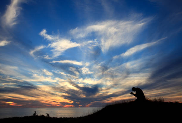 Silhouette of Man On His Knees In Prayer By The Ocean Against Beautiful Sunset Sky