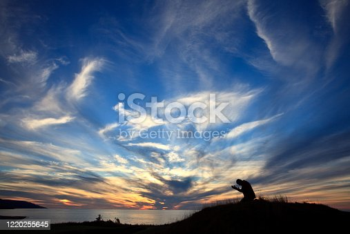 A silhouette of an unrecognizable man on his knees in prayer by the sea. Image taken in Nova Scotia, Canada. Side view. Man is in his 40s.