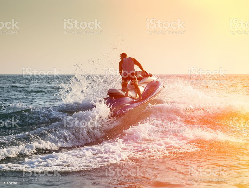 Silhouette of man on jetski at sea stock photo