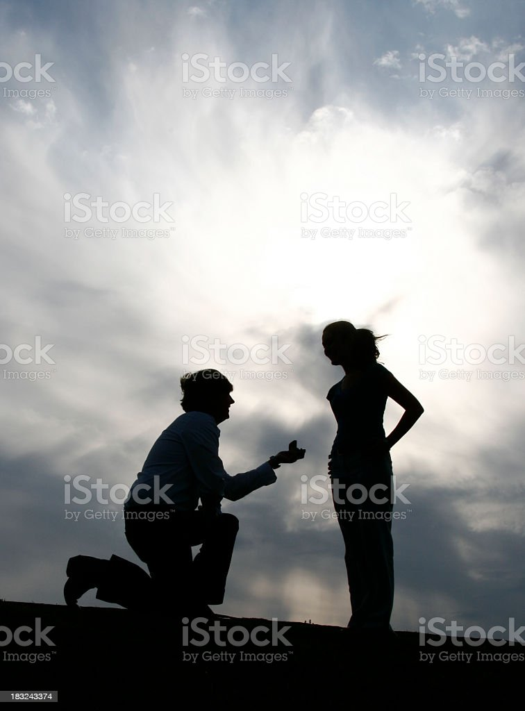 Silhouette of man on one knee to woman against hazy sky royalty-free stock photo