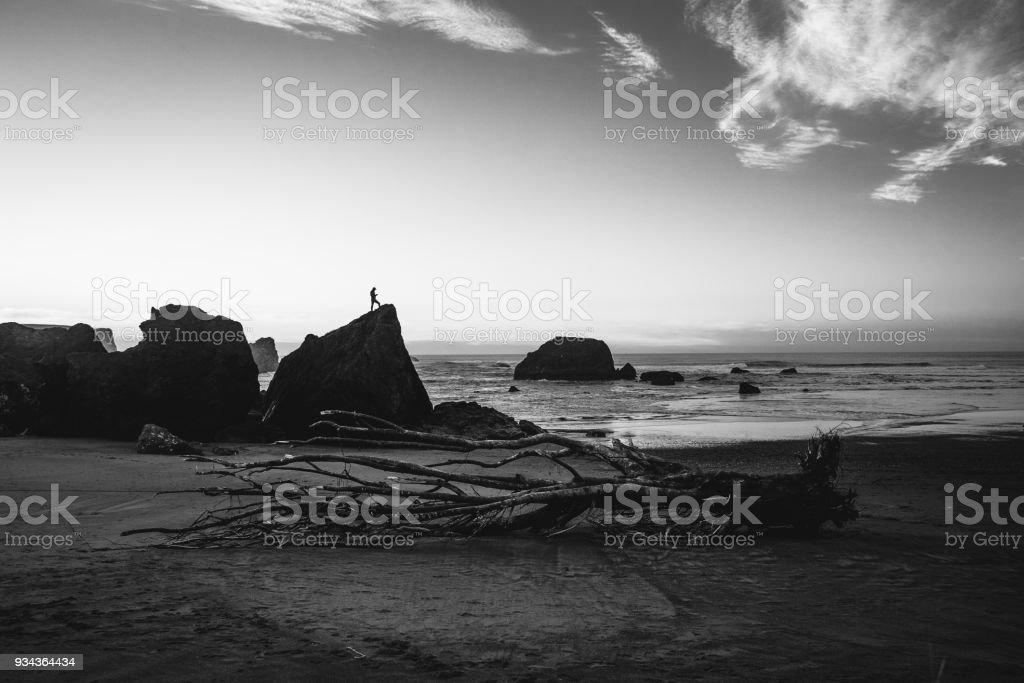 Silhouette of man on rock at sunset on Oregon Coast stock photo