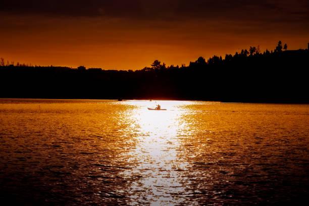 silhouette des mannes paddeln im kajak mit dramatischen sonnenuntergang. - boundary waters stock-fotos und bilder