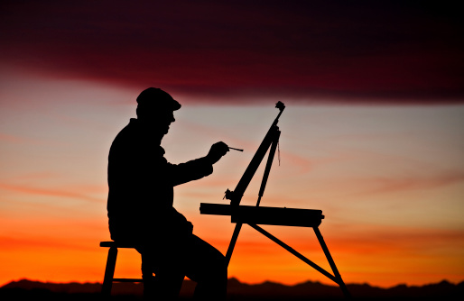 A silhouette of a man painting at sunset. The painter, or artist, is a male in his 40s. Mountains in background. Horizontal colour image. Model is wearing a painter cap and is holding his paintbrush in his right hand. Easel is tilted and the artist is painting with oil paint. He is a landscape artist. Themes include art, painting, creative, male, class, art class, art classes, student, art student, drawing, sketching, rendering, paint, paint brush, art supplies, and the arts.