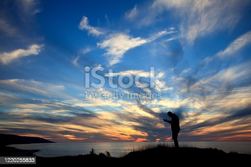 A silhouette of an unrecognizable man  in prayer by the sea. Image taken in Nova Scotia, Canada. Side view. Man is in his 40s.