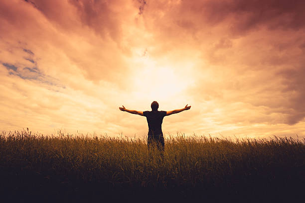 silhouette of man silhouette of man standing in a field at sunset religion stock pictures, royalty-free photos & images