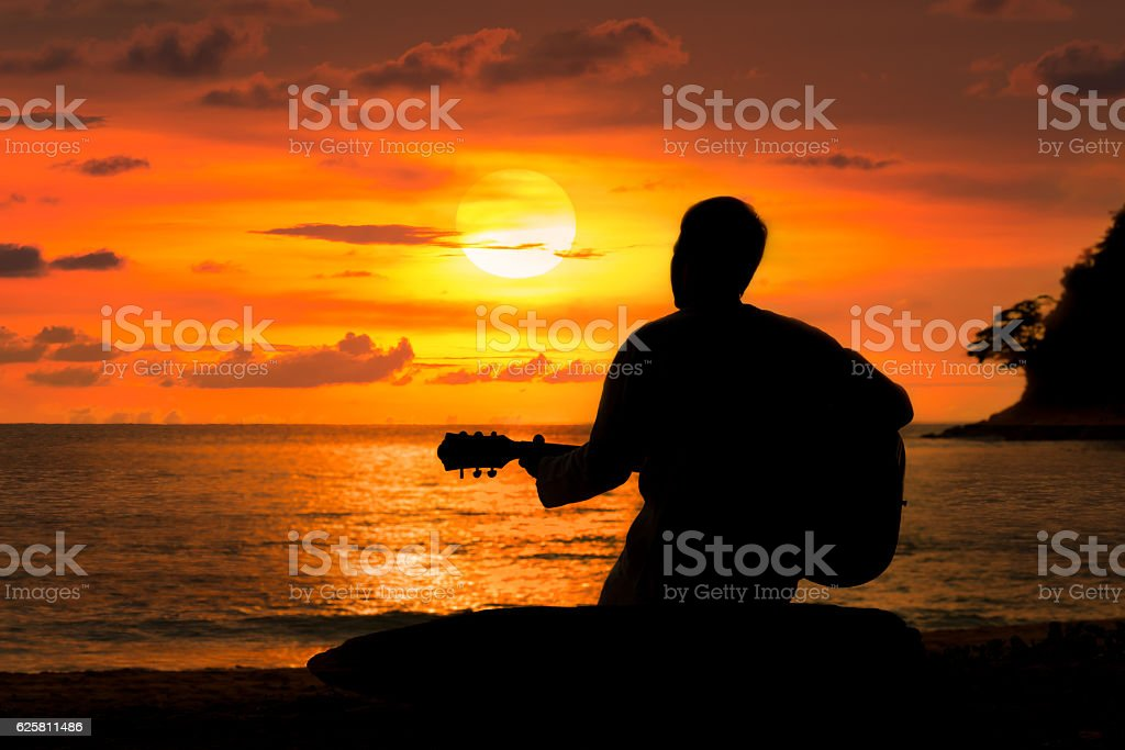 Silhouette of man playing a guitar at sunset  A stock photo