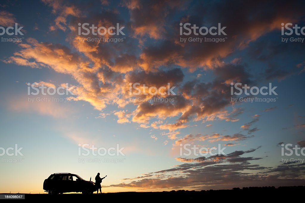 Silhouette of Man Playing Guitar Standing Beside Car royalty-free stock photo