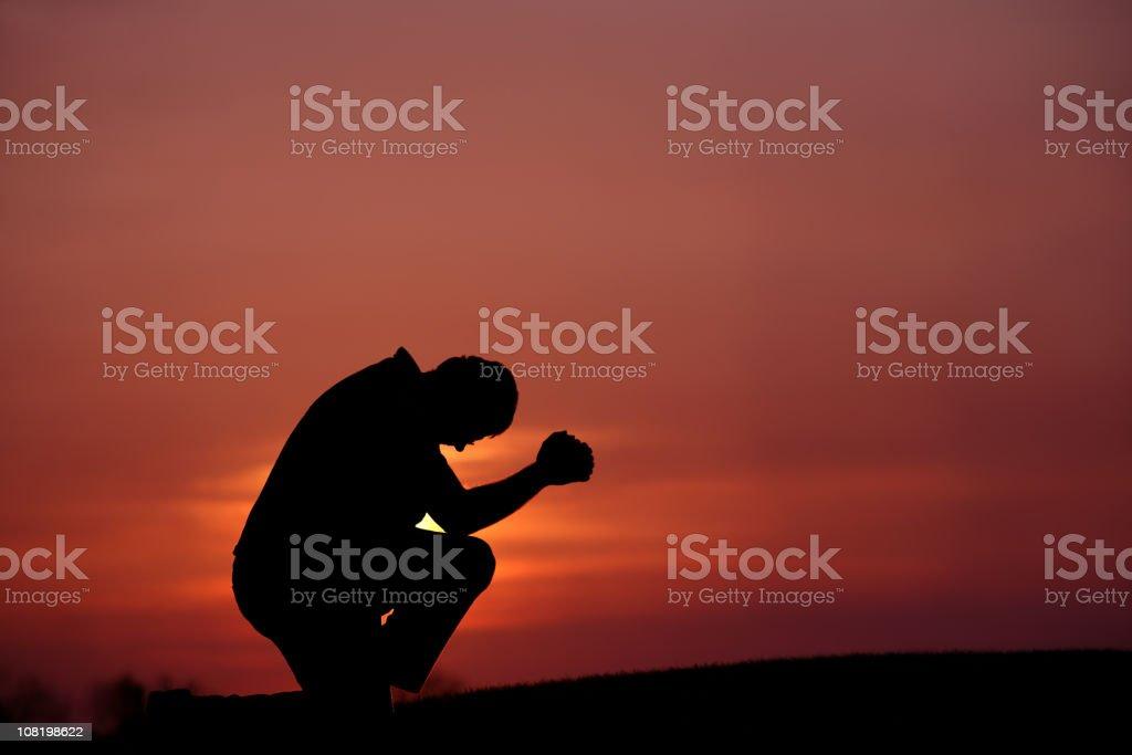 Silhouette of Man Praying at Dusk royalty-free stock photo