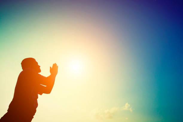 Silhouette of man praying at sunrise. stock photo