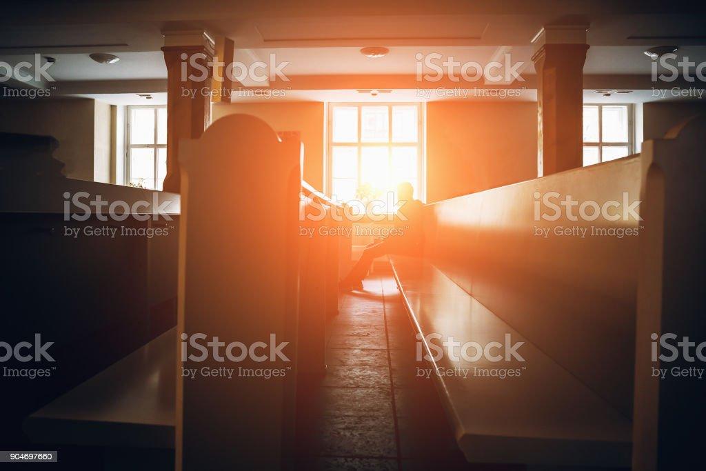 Silhueta de homem rezando na igreja em luz do sol - foto de acervo