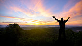 Silhouette of man raised hands with landscape mountains at sunset