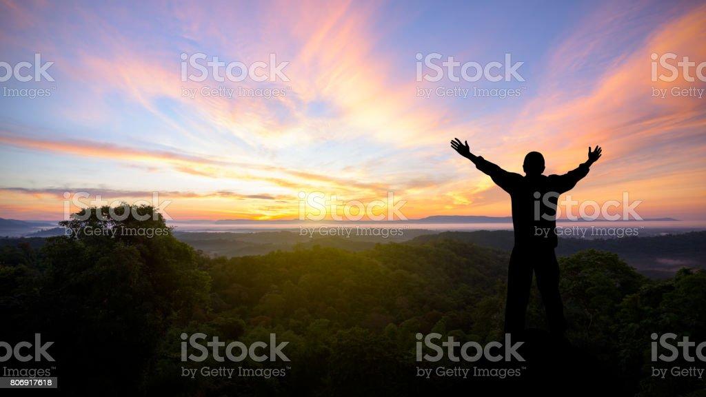 Silhueta de homem levantou as mãos com montanhas de paisagem ao pôr do sol - foto de acervo