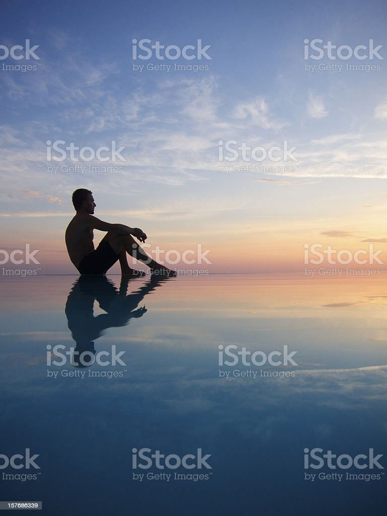 Silhouette of Man Reflecting in Infinity Pool at Sunset royalty-free stock photo