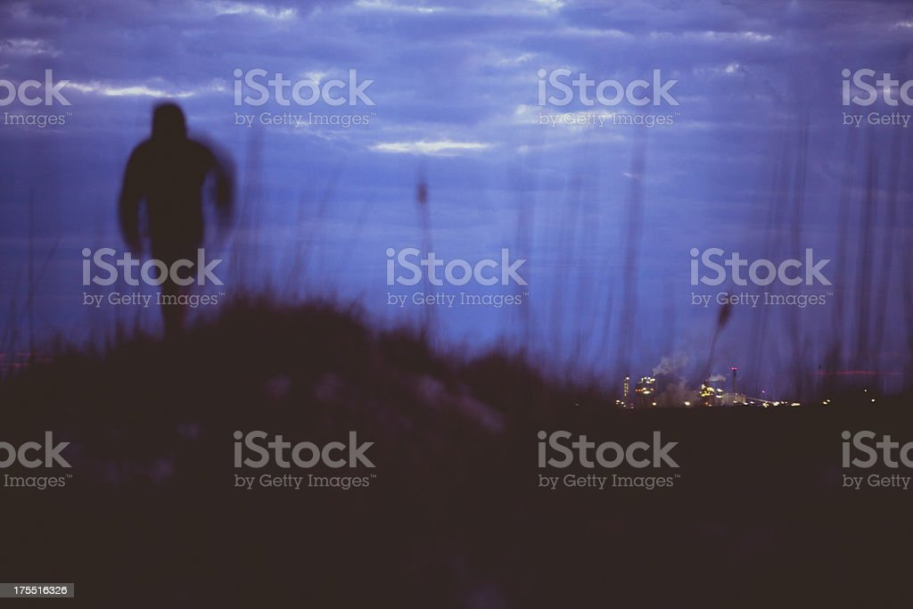 Silhouette of man running along coastline with skyline in distance royalty-free stock photo