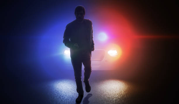 Silhouette of man running away from police car at night. stock photo