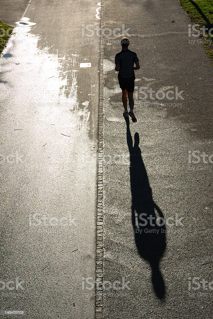 silhouette of man running, back lit, shadow on wet pavement stock photo