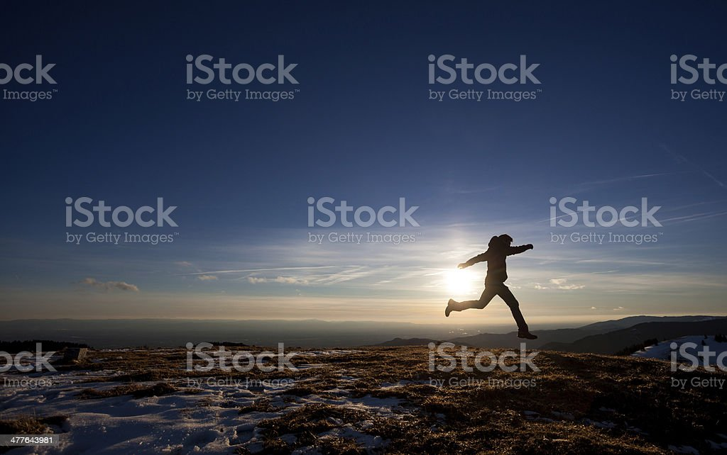 silhouette of man running in sunset sky stock photo