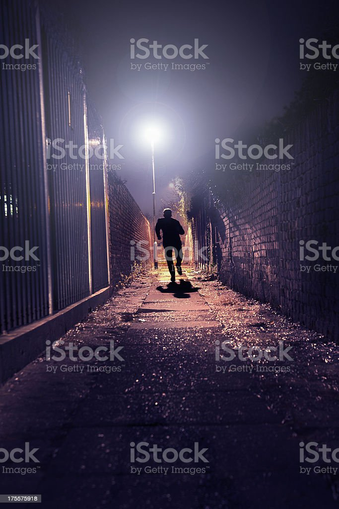 silhouette of man running through dark alley. stock photo
