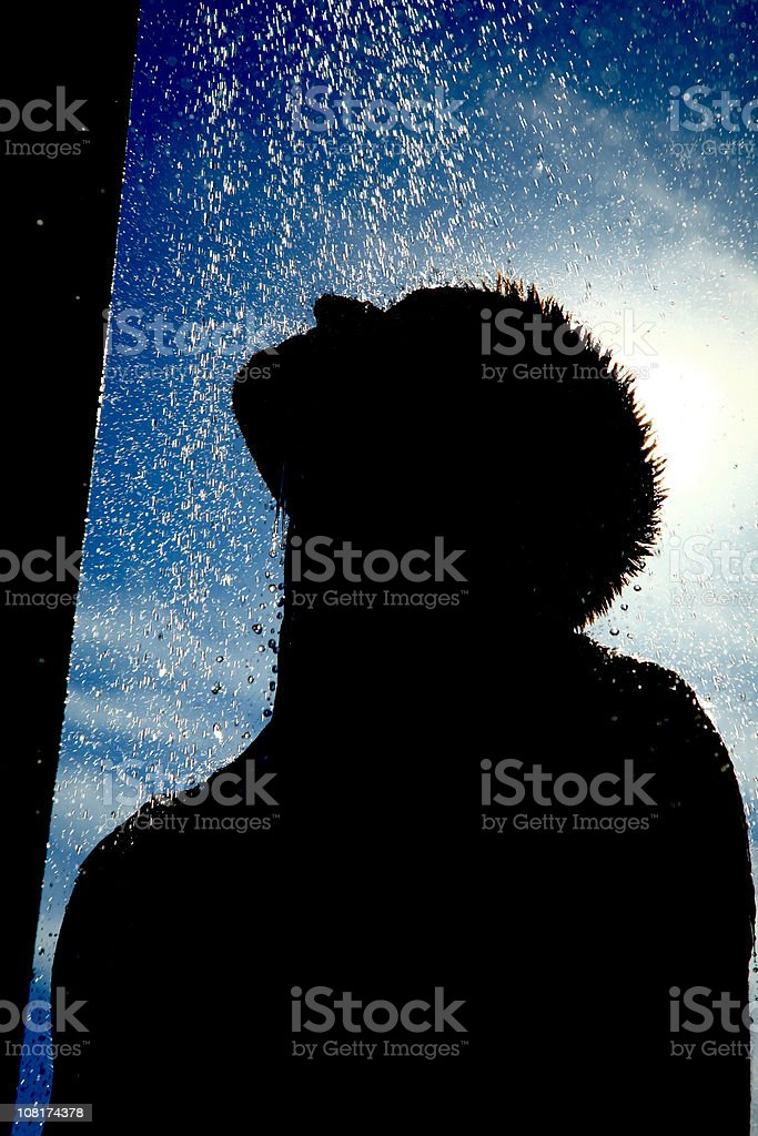 Silhouette of Man Showering with Blue Sky in Background royalty-free stock photo