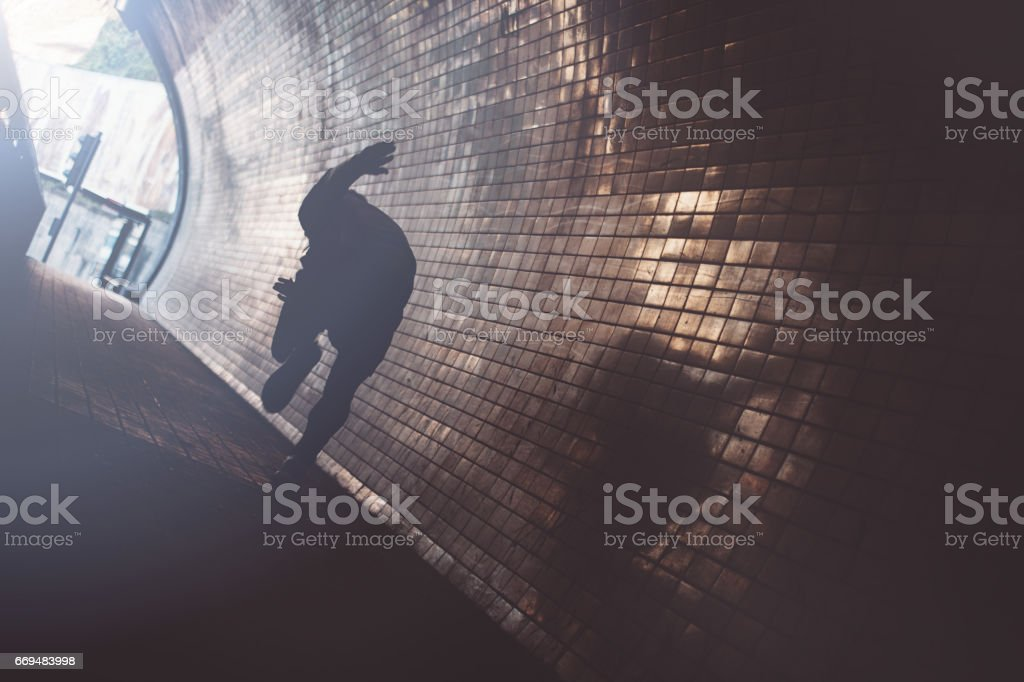 Silhouette of man sprinting in the dark tunnel stock photo