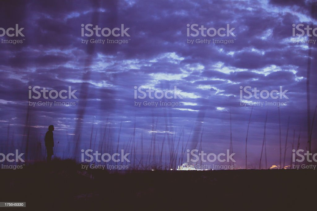 Silhouette of man standing on coastline at sunset royalty-free stock photo