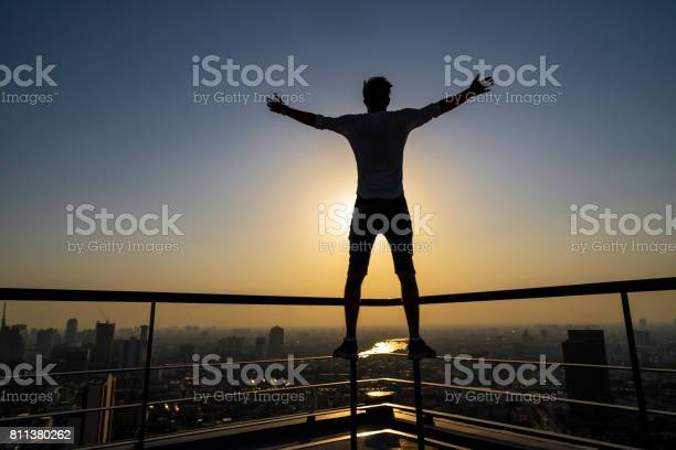 Silhouette of man standing with extend arms action over the cityscape picture id811380262?b=1&k=6&m=811380262&s=612x612&h=xcnzga16zwj5gdxbtroncjqep0norqd6ebioto ky8c=