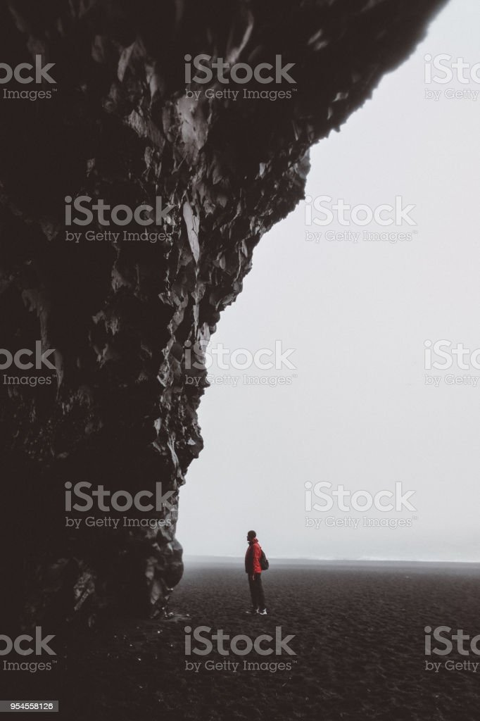 Silhouette of man staying in basalt cave on black sand beach in Iceland stock photo