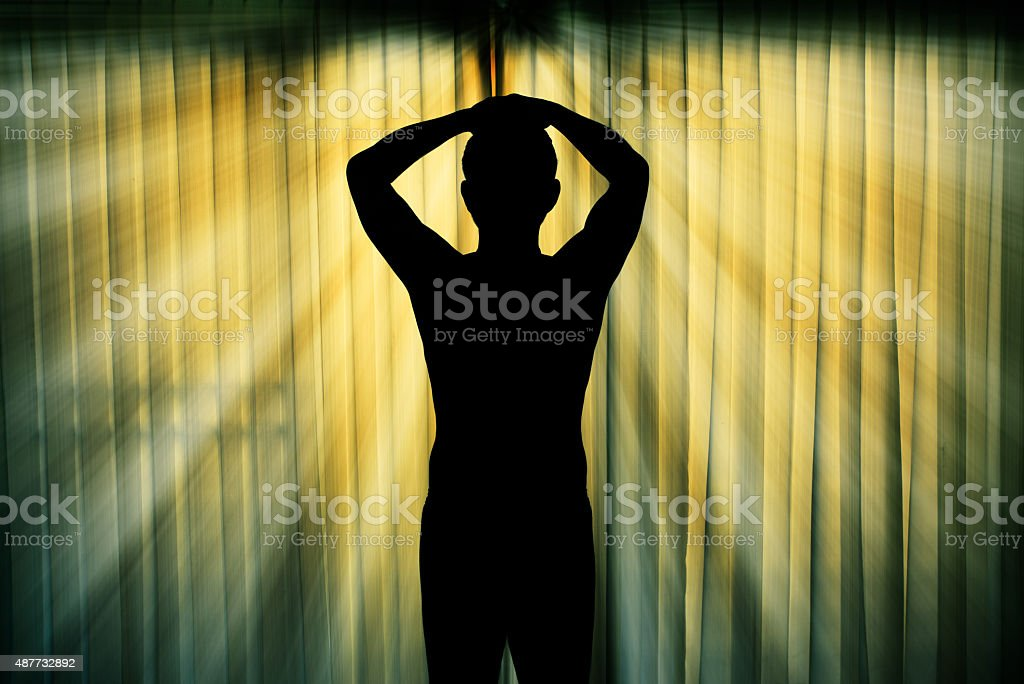 Silhouette of man surrendering with two hands raised in air stock photo