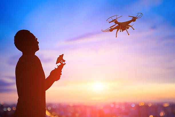 silhouette of man take drone - drones stock photos and pictures