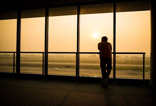 Silhouette of man waiting for the flight stock photo