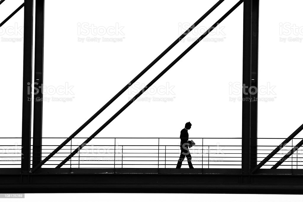 Silhouette of Man Walking Down Walkway royalty-free stock photo