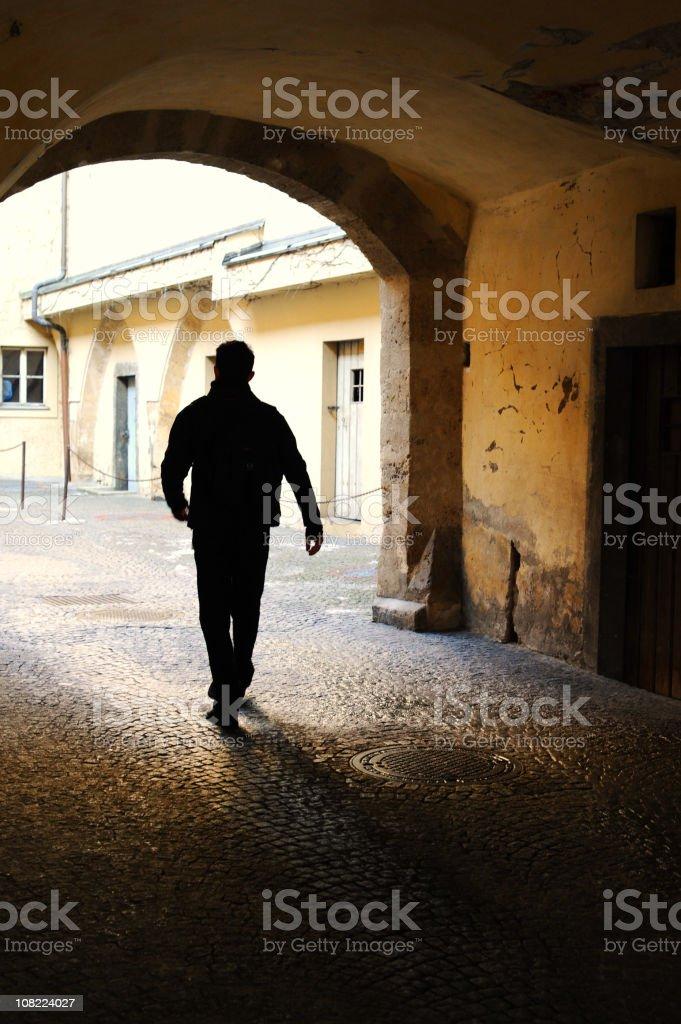 Silhouette of man walking in street royalty-free stock photo